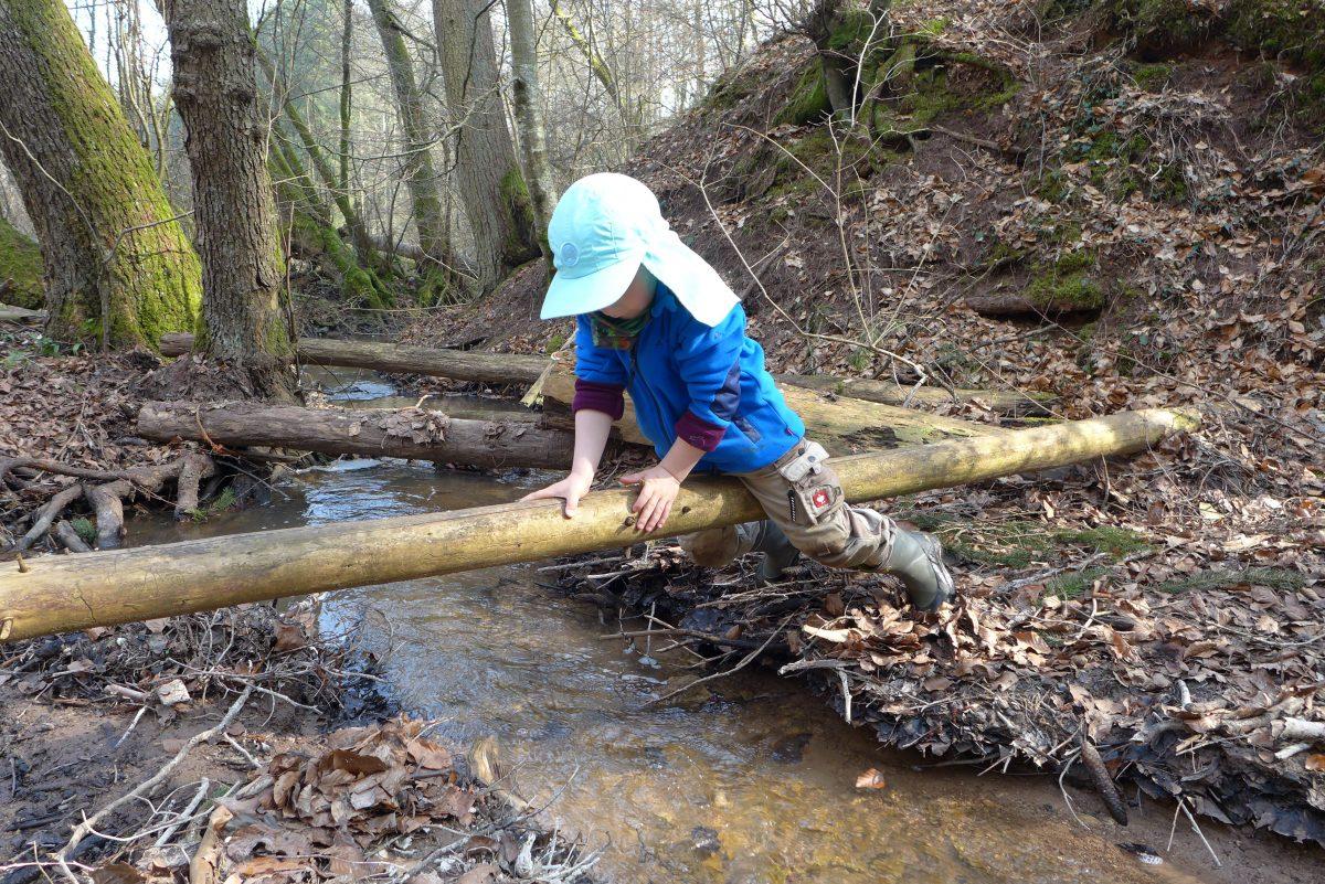 Kind rutscht auf Balken über einen Bach